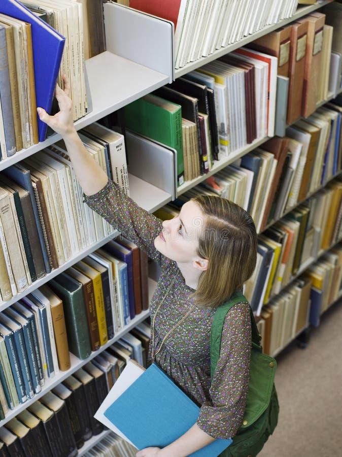 Молодая женщина достигая для книги от полки библиотеки стоковая фотография rf