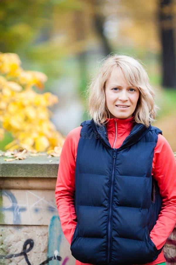 Молодая женщина ослабляя в парке осени стоковые фотографии rf