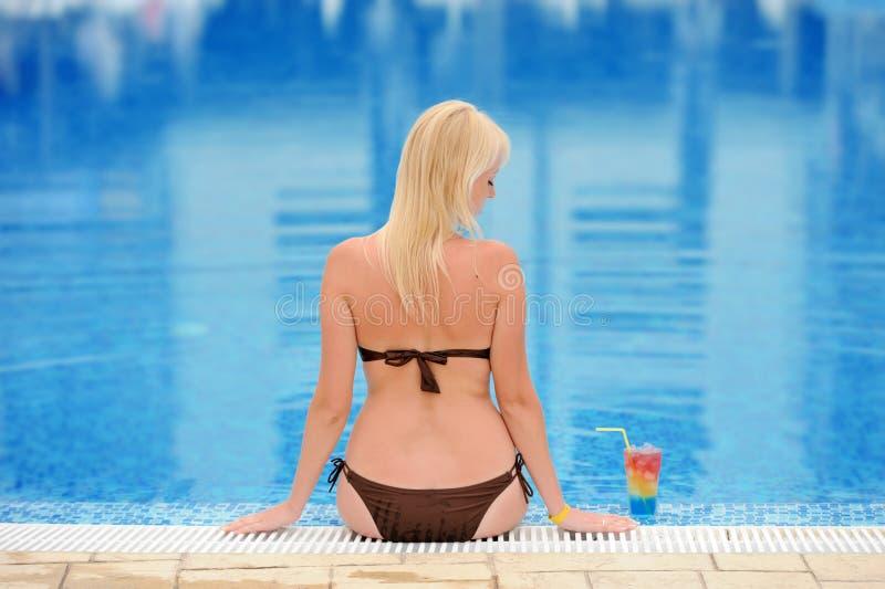Молодая женщина ослабляя на бассейне с коктеилем стоковые изображения