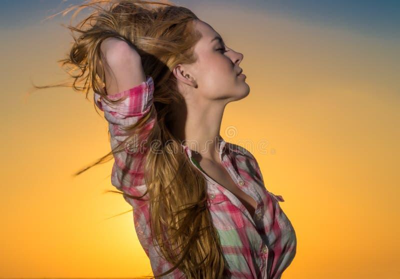 Молодая женщина ослабляя на заходе солнца стоковое фото