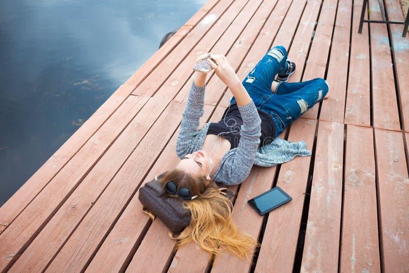 Молодая женщина ослабляя на пристани стоковые изображения