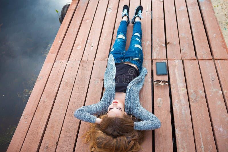 Молодая женщина ослабляя на пристани стоковое фото