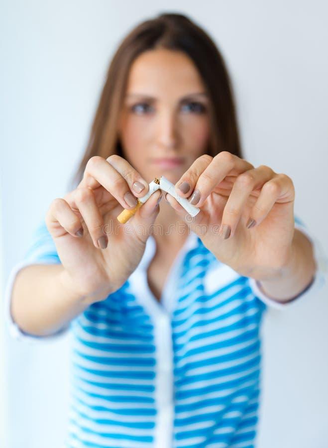 Молодая женщина отказывает курить и ломает сигарету стоковые изображения rf