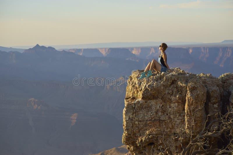 Молодая женщина отдыхая на скале после пешего туризма, гранд-каньоне стоковое фото