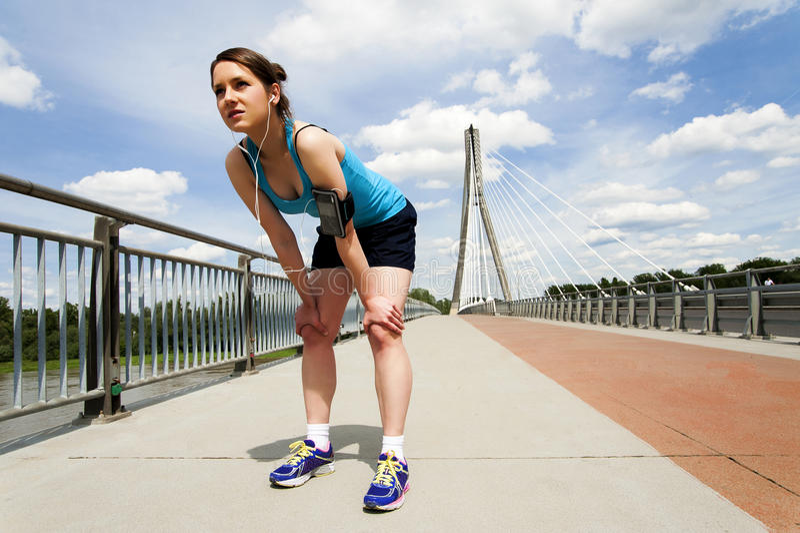 Молодая женщина отдыхая после бега в голубом sportswear над brid стоковые изображения