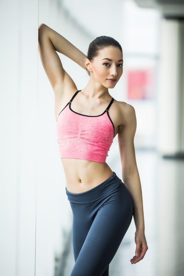 Молодая женщина отдыхая после разминки на спортзале около окна Женщина фитнеса принимая пролом после встречи в оздоровительном кл стоковая фотография