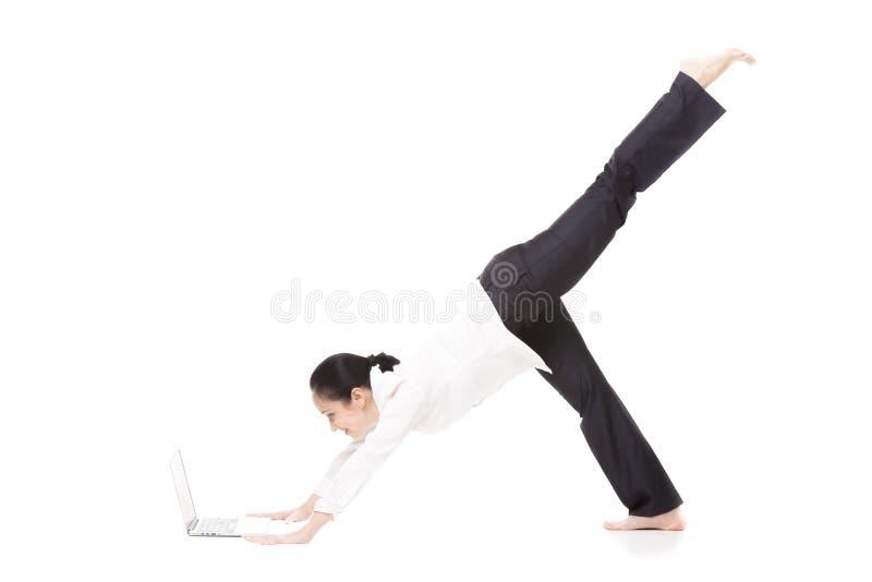 Молодая женщина офиса в представлении йоги держа компьтер-книжку на белом backgrou стоковые фото