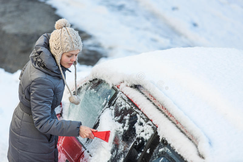 Молодая женщина очищая ее автомобиль от снега и заморозка стоковое фото rf