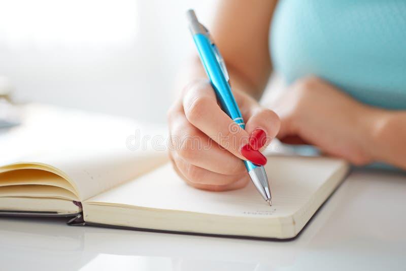 Молодая женщина пишет к черному дневнику стоковые фото