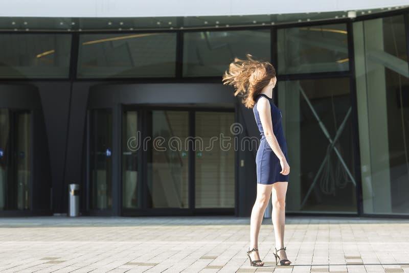 Молодая женщина поворачивая его волосы головы развевая, стоя на заднем плане делового центра стоковые фото