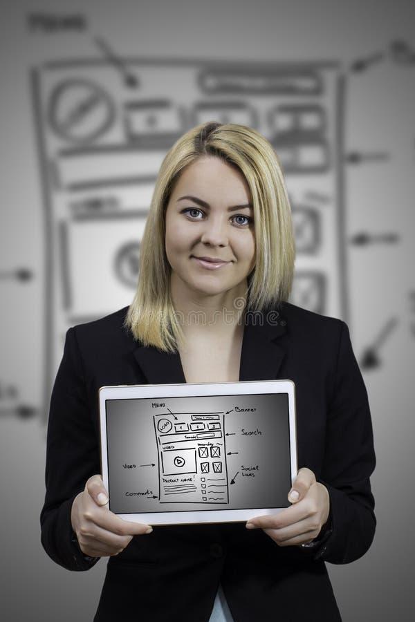 Молодая женщина показывая эскиз провод-рамки вебсайта на таблетке стоковое изображение