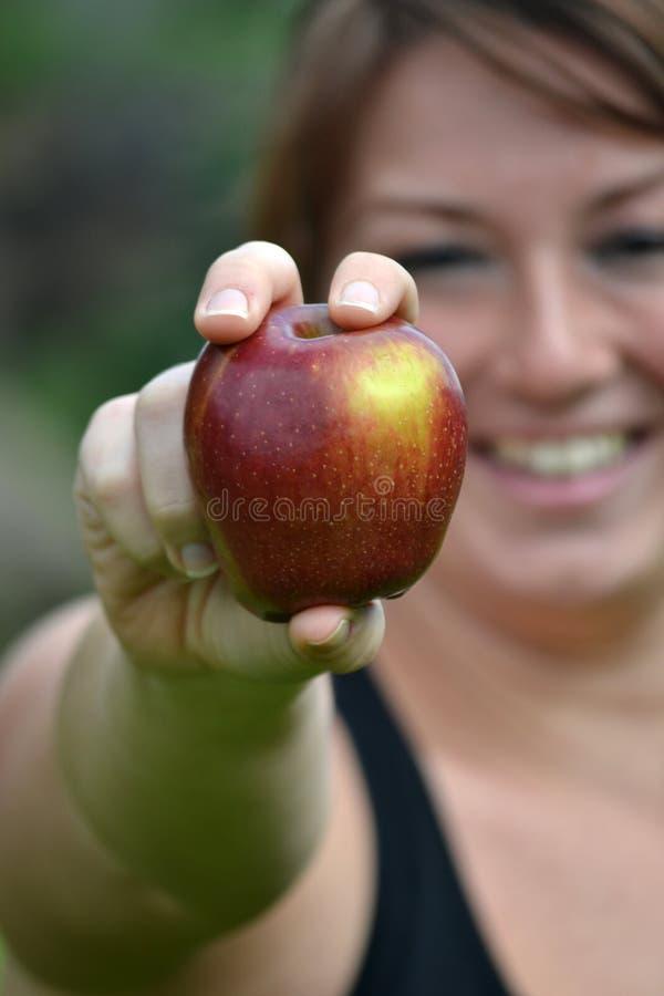 Молодая женщина показывая яблоко стоковое изображение rf
