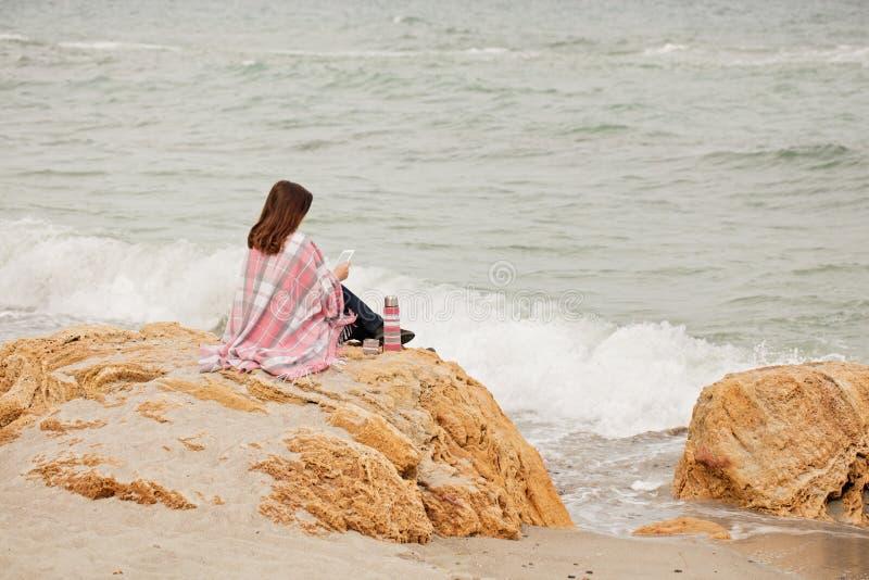 Молодая женщина покрыта с половиком сидит на seashore и читает стоковое фото