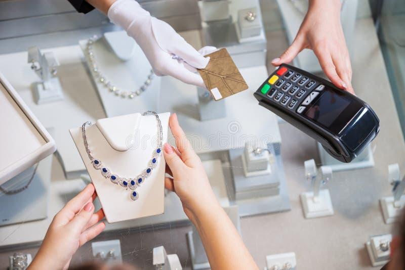 Молодая женщина покупая золотое ожерелье с голубыми драгоценными камнями стоковые фото