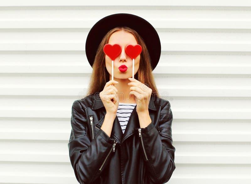 Молодая женщина портрета моды довольно сладостная при красные губы делая поцелуй воздуха с курткой черной шляпы сердца леденца на стоковая фотография