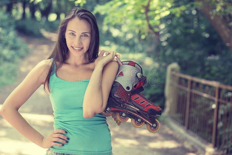 Молодая женщина портрета счастливая идя rollerblading держать в линии катается на коньках стоковые изображения rf