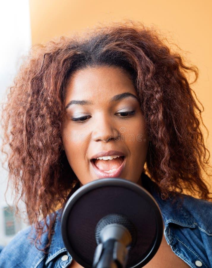 Молодая женщина поя в студии звукозаписи стоковая фотография