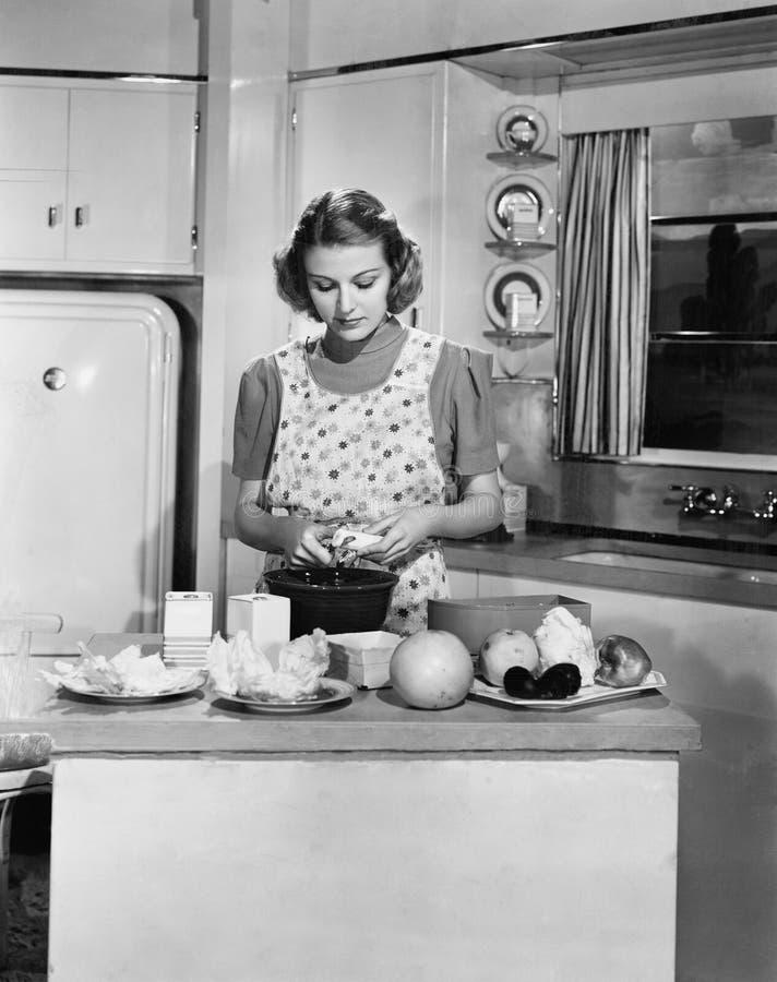 Молодая женщина подготавливая еду в кухне (все показанные люди более длинные живущие и никакое имущество не существует Гарантии t стоковая фотография rf