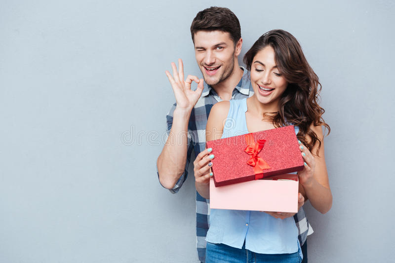 Молодая женщина получая подарок от ее парня над серой предпосылкой стоковое фото rf