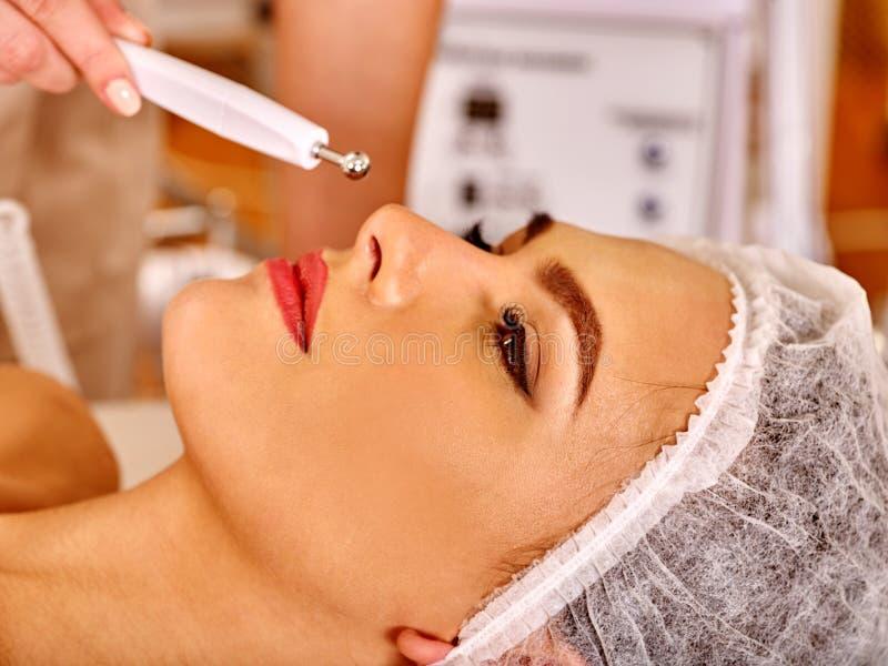 Молодая женщина получая электрический лицевой массаж стоковое изображение
