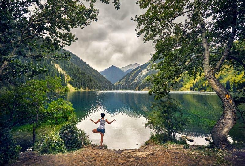 Молодая женщина практикует йогу outdoors стоковое фото