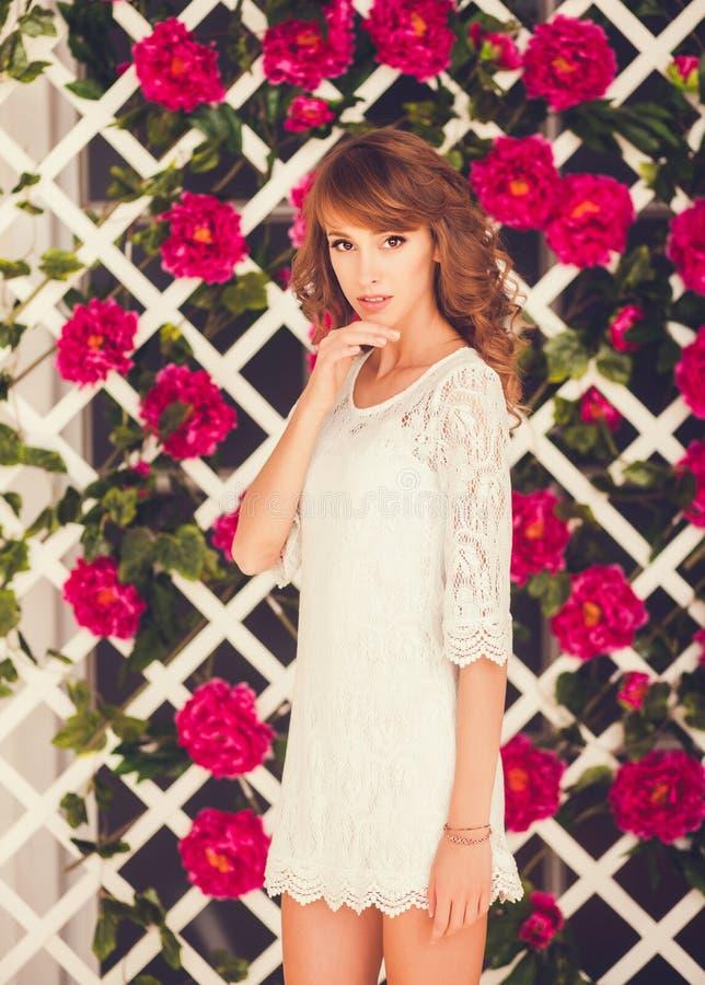 Молодая женщина представляя в белом платье стоковые фото