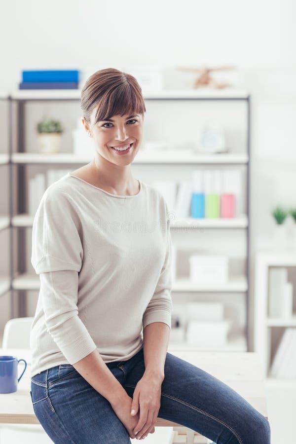 Молодая женщина представляя в ее офисе стоковая фотография