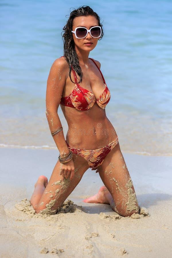 Молодая женщина представляя на пляже стоковое изображение rf