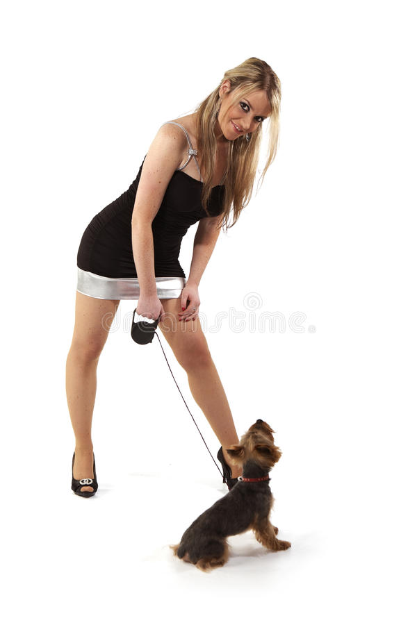 Молодая женщина представляя с ее собакой стоковое фото