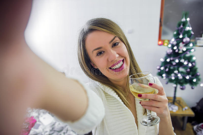Молодая женщина представляя для selfie рождества Молодая усмехаясь женщина в шляпе рождества делая фото selfie с игристым вином стоковое изображение rf