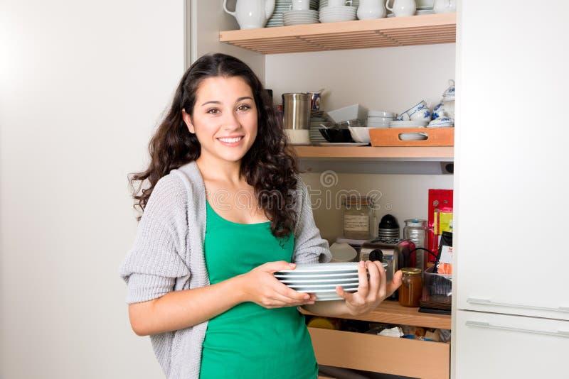 Молодая женщина принимая вне посуду шкафа для того чтобы установить таблицу стоковая фотография rf