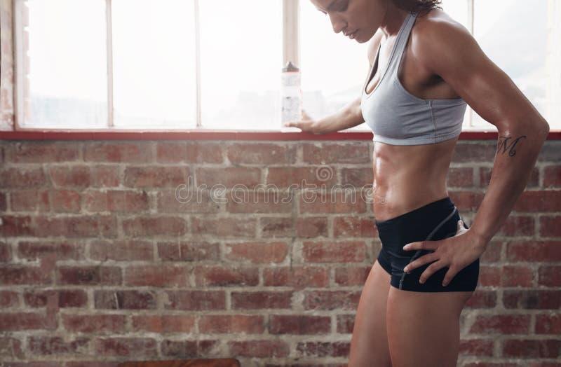 Молодая женщина принимая пролом от разминки на спортзал стоковое изображение