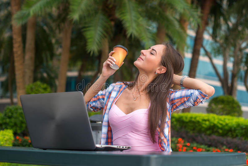 Молодая женщина принимая пролом для того чтобы ослабить от работы на компьтер-книжке в парке пока держащ чашку кофе в одной руке  стоковое изображение rf