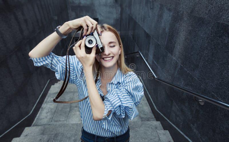 Молодая женщина принимая фото, на старой камере фильма, день, внешний стоковая фотография rf