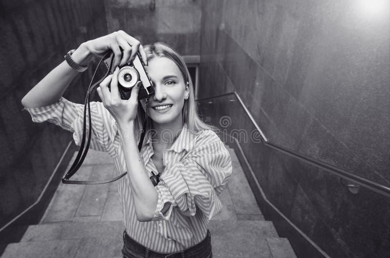 Молодая женщина принимая фото, на старой камере фильма, день, внешний стоковые фотографии rf