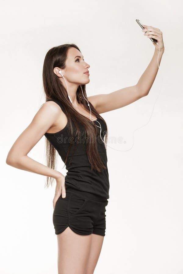 Молодая женщина принимая selfie на спортзал стоковое изображение