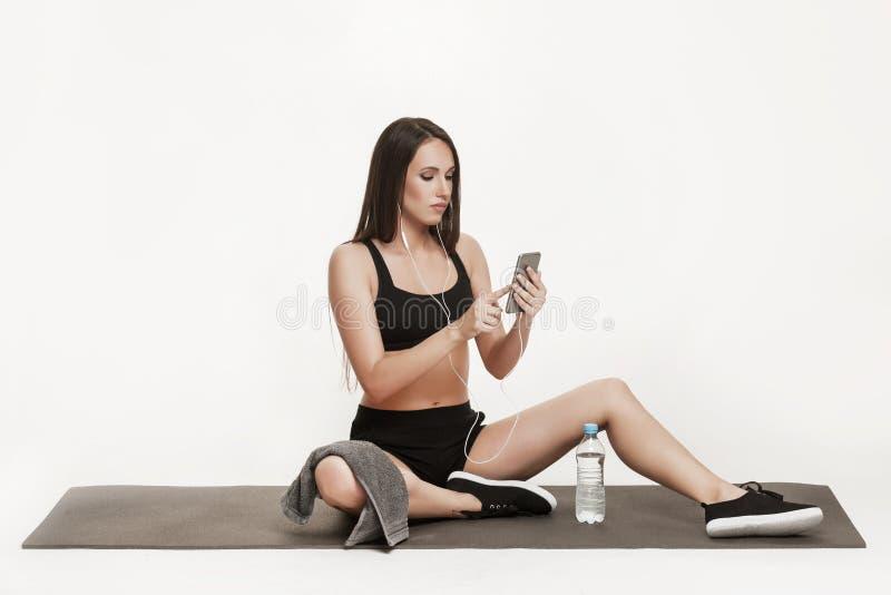 Молодая женщина принимая selfie на спортзал стоковое фото