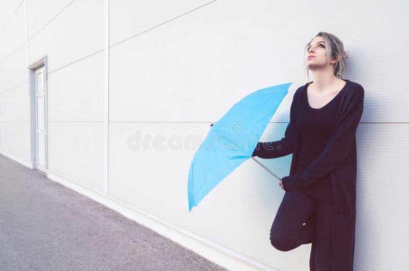 Молодая женщина при голубой зонтик ждать дождь стоковые изображения rf