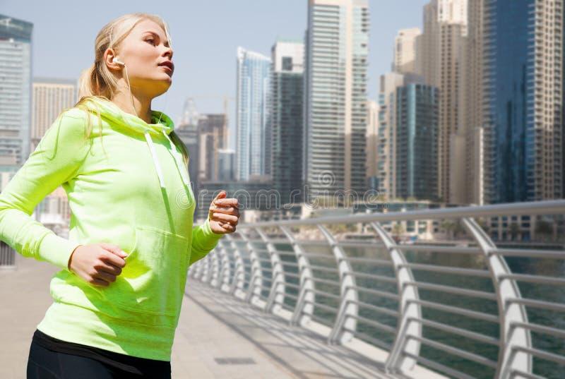 Молодая женщина при наушники jogging outdoors стоковые изображения rf