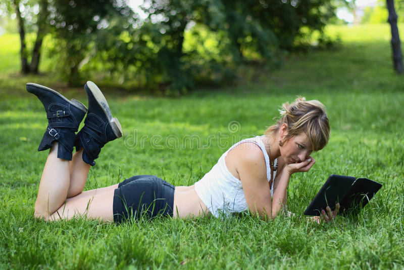 Молодая женщина при таблетка ослабляя на травянистой земле стоковые изображения rf
