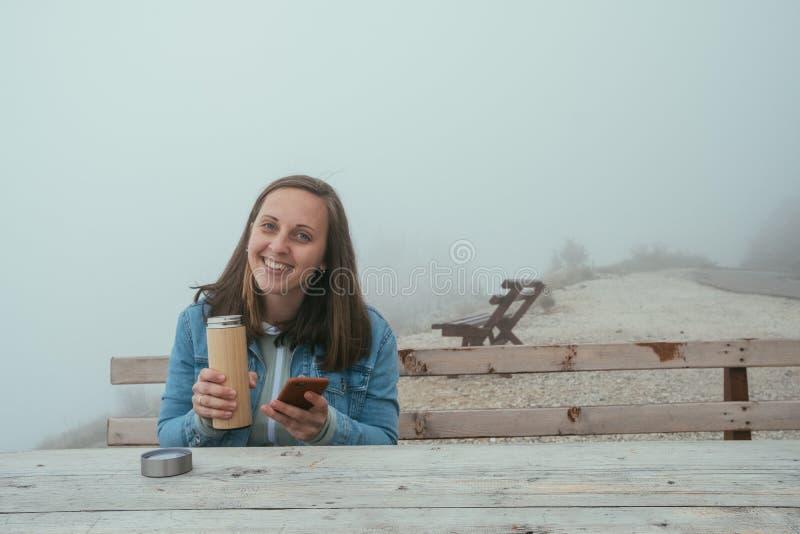 Молодая женщина при телефон сидя на деревянной скамье и выпивать горячий стоковое фото rf