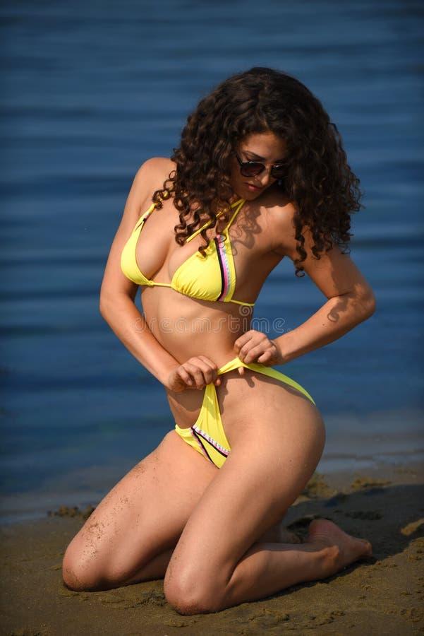 Молодая женщина при тонкое и подходящее тело нося желтый представлять бикини сексуальный на тропическом пляже стоковое фото rf