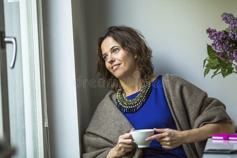 Молодая женщина при чашка чаю сидя на таблице около окна Счастливый стоковая фотография