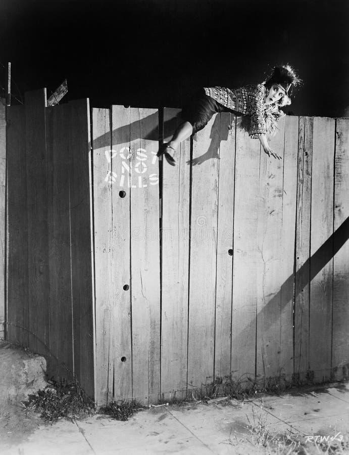 Молодая женщина пробуя взобраться над деревянной загородкой (все показанные люди более длинные живущие и никакое имущество не сущ стоковое фото rf