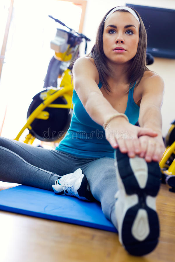 Молодая женщина протягивая ее ногу для того чтобы нагревать в спортзале стоковые фото