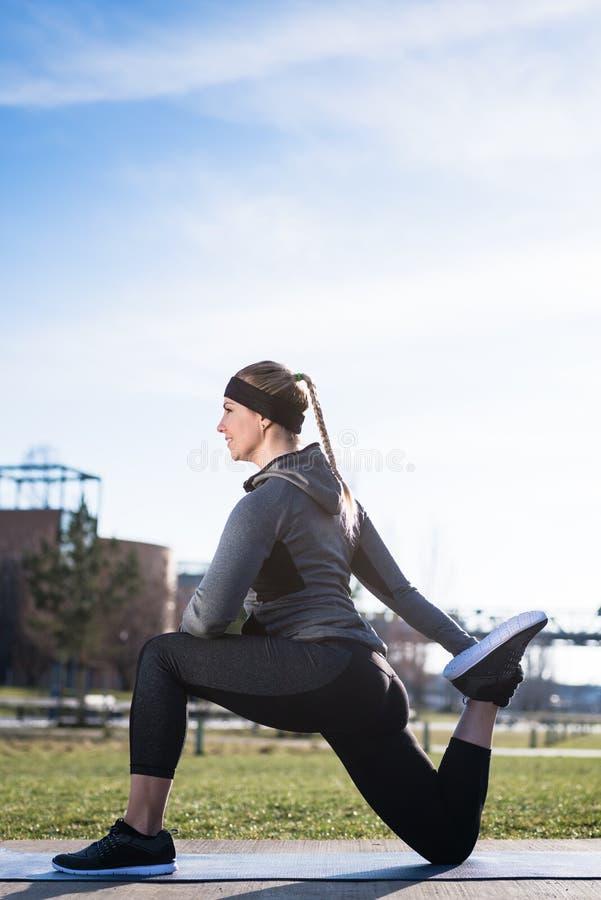 Молодая женщина протягивая ее quadriceps muscles путем хватать ее стоковые изображения rf