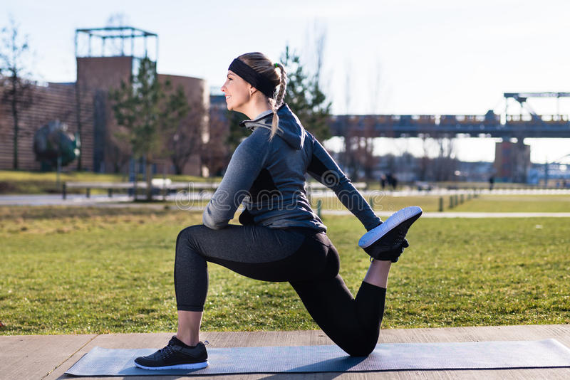 Молодая женщина протягивая ее quadriceps muscles путем хватать ее стоковые изображения