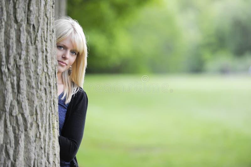 Молодая женщина пряча за деревом стоковая фотография rf