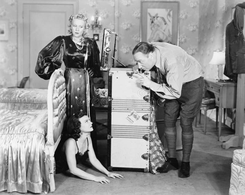 Молодая женщина пряча под кроватью и пара стоя около ее (все показанные люди более длинные живущие и никакое имущество не существ стоковое фото rf