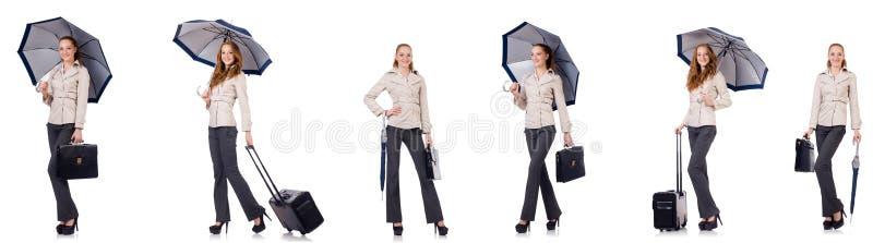 Молодая женщина путешествуя при чемодан и зонтик изолированные на wh стоковая фотография